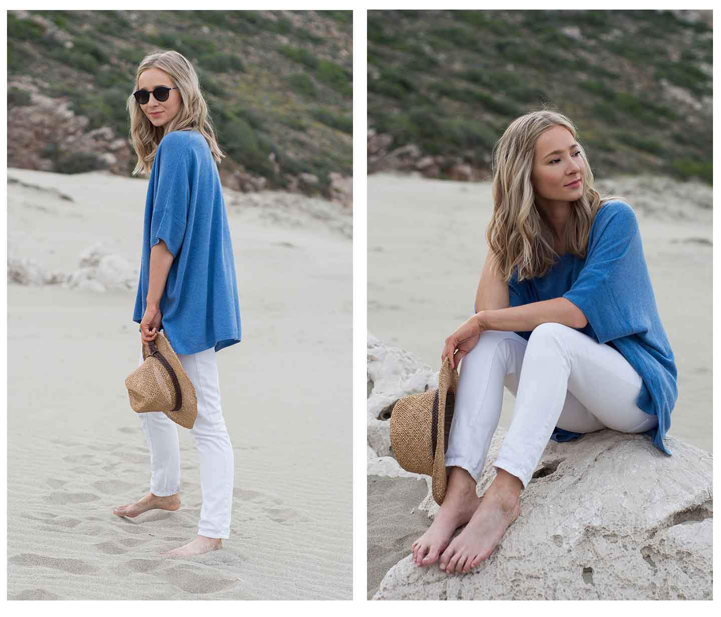 woman-on-beach-wearing-a-blue-cashmere-kimono-jumper-with-white-jeans-sunglasses-and-a-straw-hat