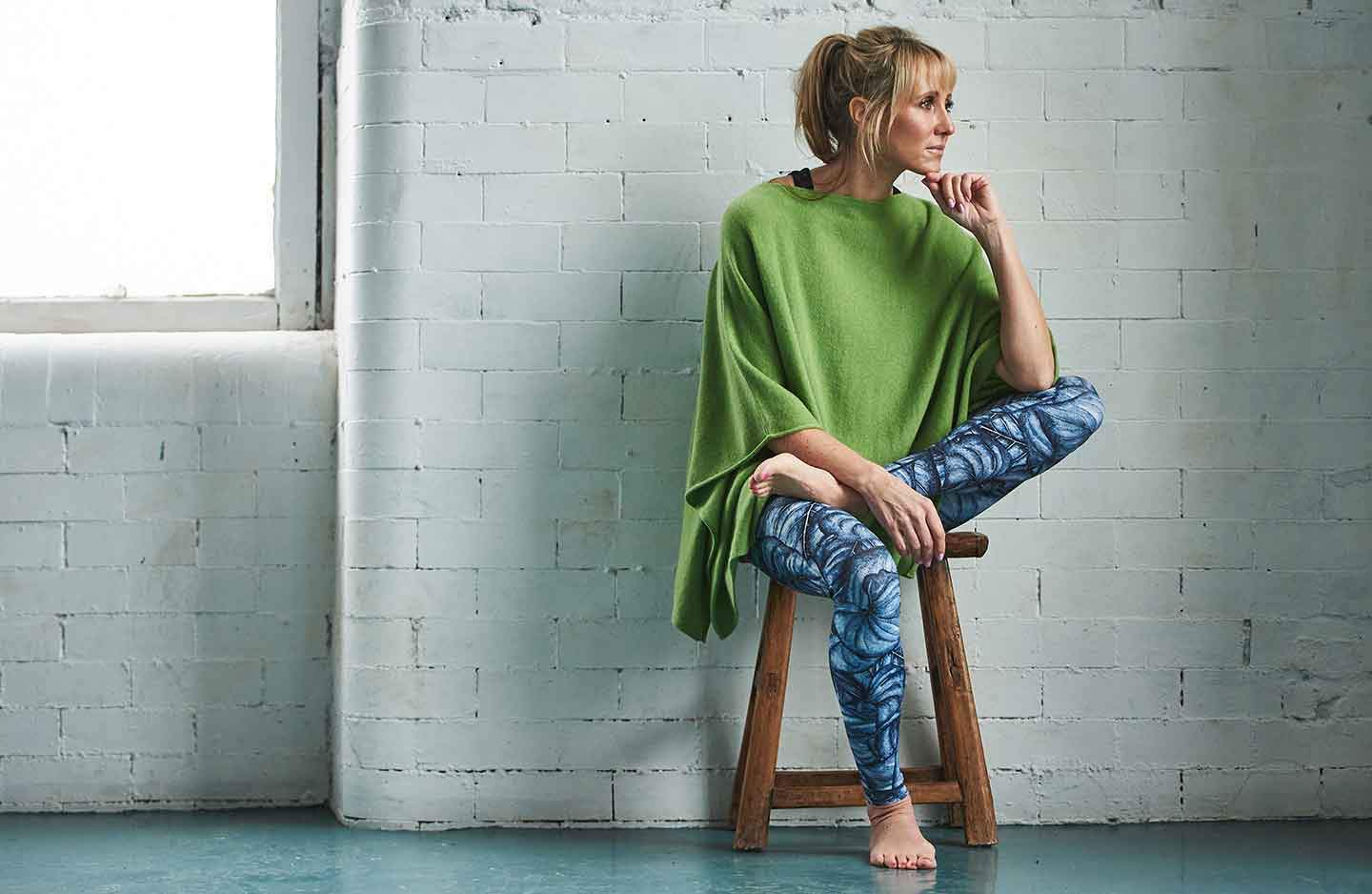 women-sitting-infront-of-a-white-brick-wall-on-a-wooden-stool-wearing-green-cashmere-oversized-poncho-over-sportswear