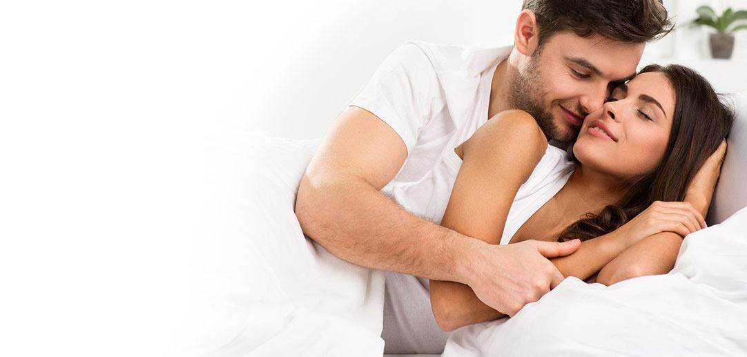Man and woman hugging in bed