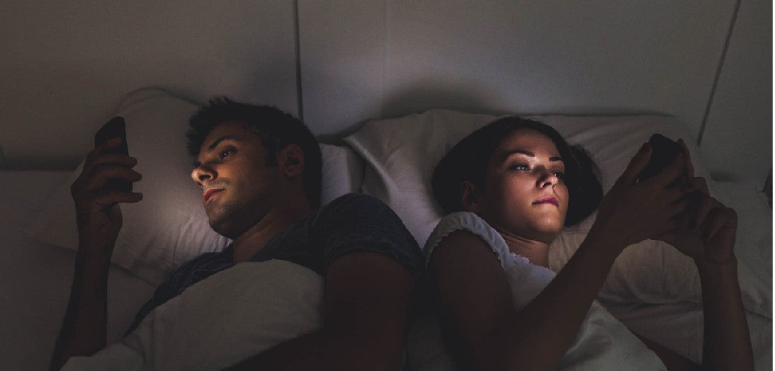 Man and woman in bed on smartphones
