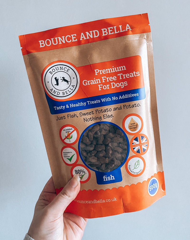 A Packet of Grain Free Fish Training Treats for Dogs being held up against a grey background.