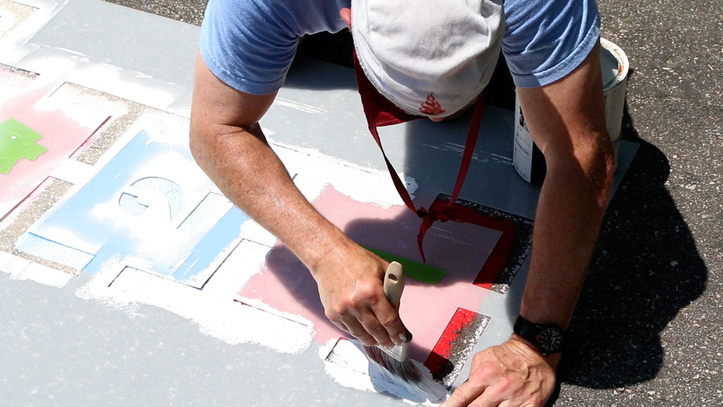 Use a brush to paint pavement paint through the stencil