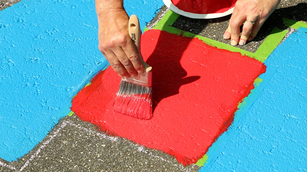 Brush the second coat of paint through the stencil between the blue sections