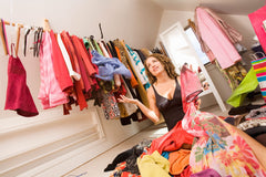 an image of a woman sitting in a messy closet
