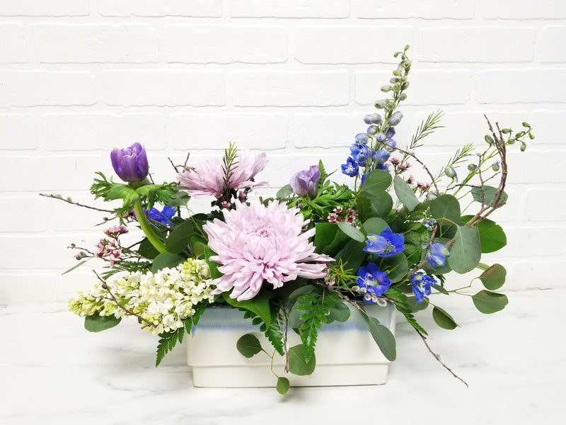Flower arrangement with purples, blues, and whites in a white vase against a white background.