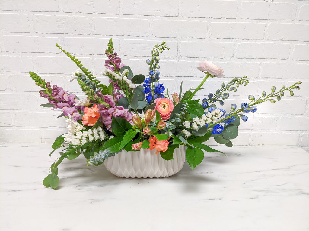 Full flower arrangement in a textured white vase. Pink, purple, blue, and white flowers.