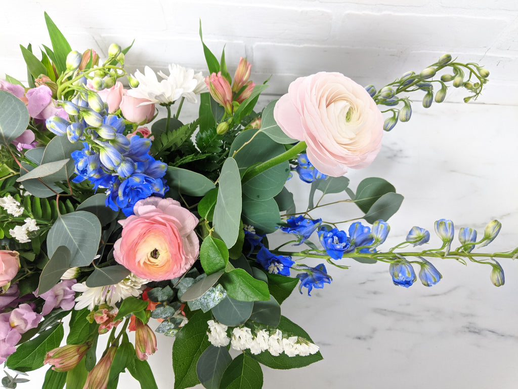 Top-down, close-up photo of the light pink, blue, and white flowers, and green leaves.