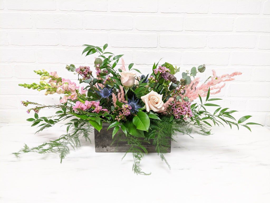 Flowers bursting out of a wooden-looking vase. Bunches of leaves and pink flowers, and blue accents.