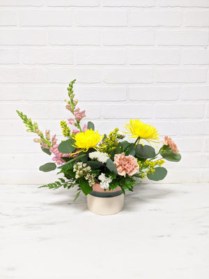 Multi-toned pink vase with tall green leaves, yellow flowers, pink, and white flowers.