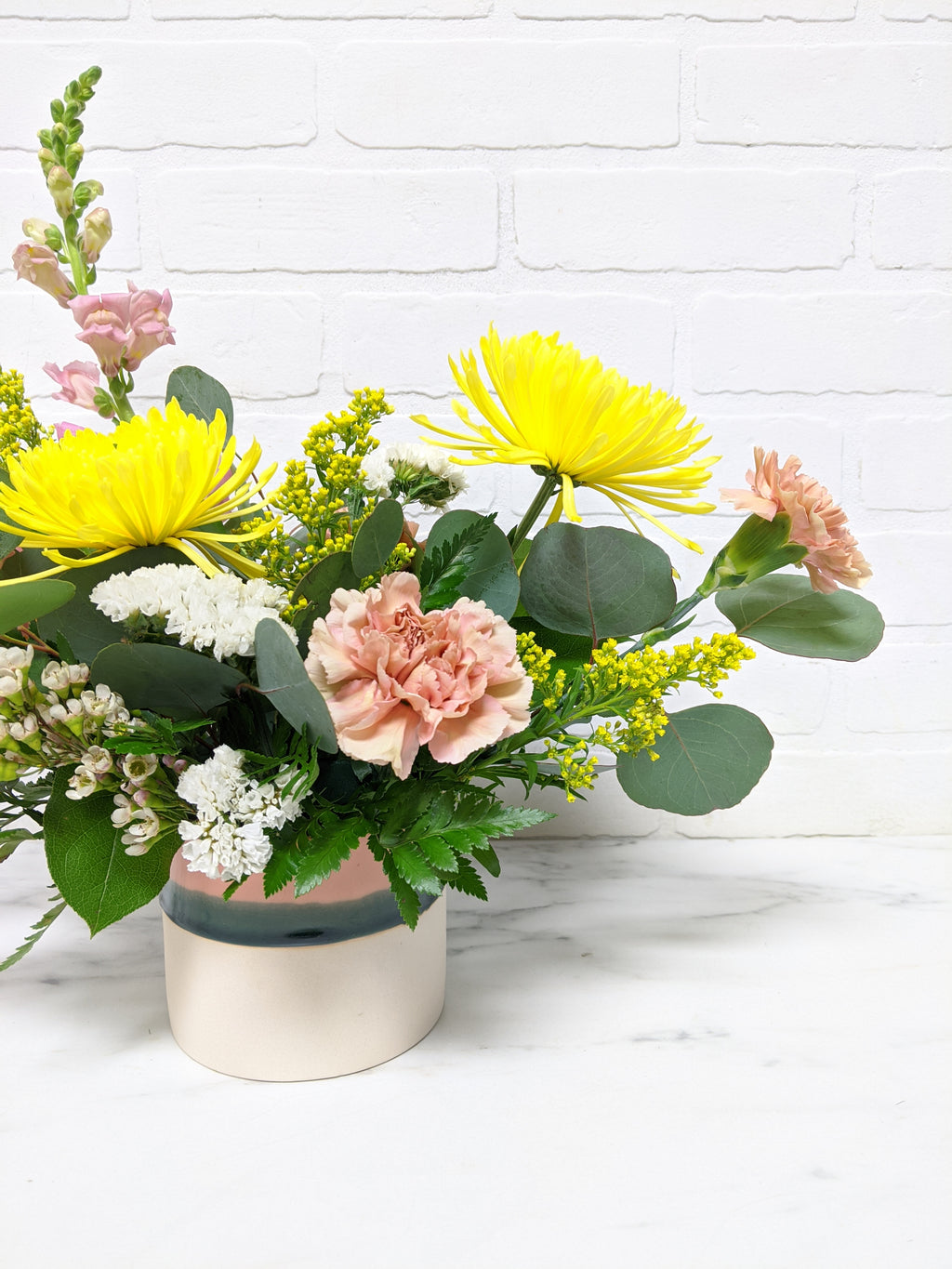 Closer view of yellow and white accent flowers, larger yellow and pink flowers, and green leaves.