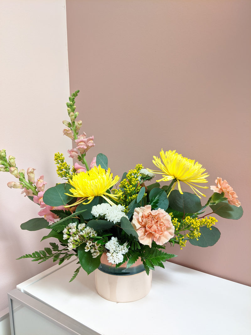 Angled photo of flower arrangement against a pink and purple wall, similarly coloured to the vase.