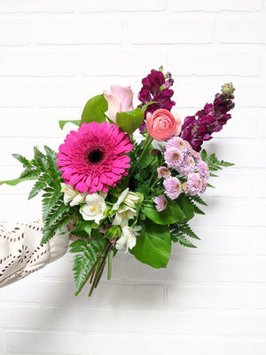 Hand holding a vibrant pink and purple bouquet, with green textured leaves and white accent flowers.