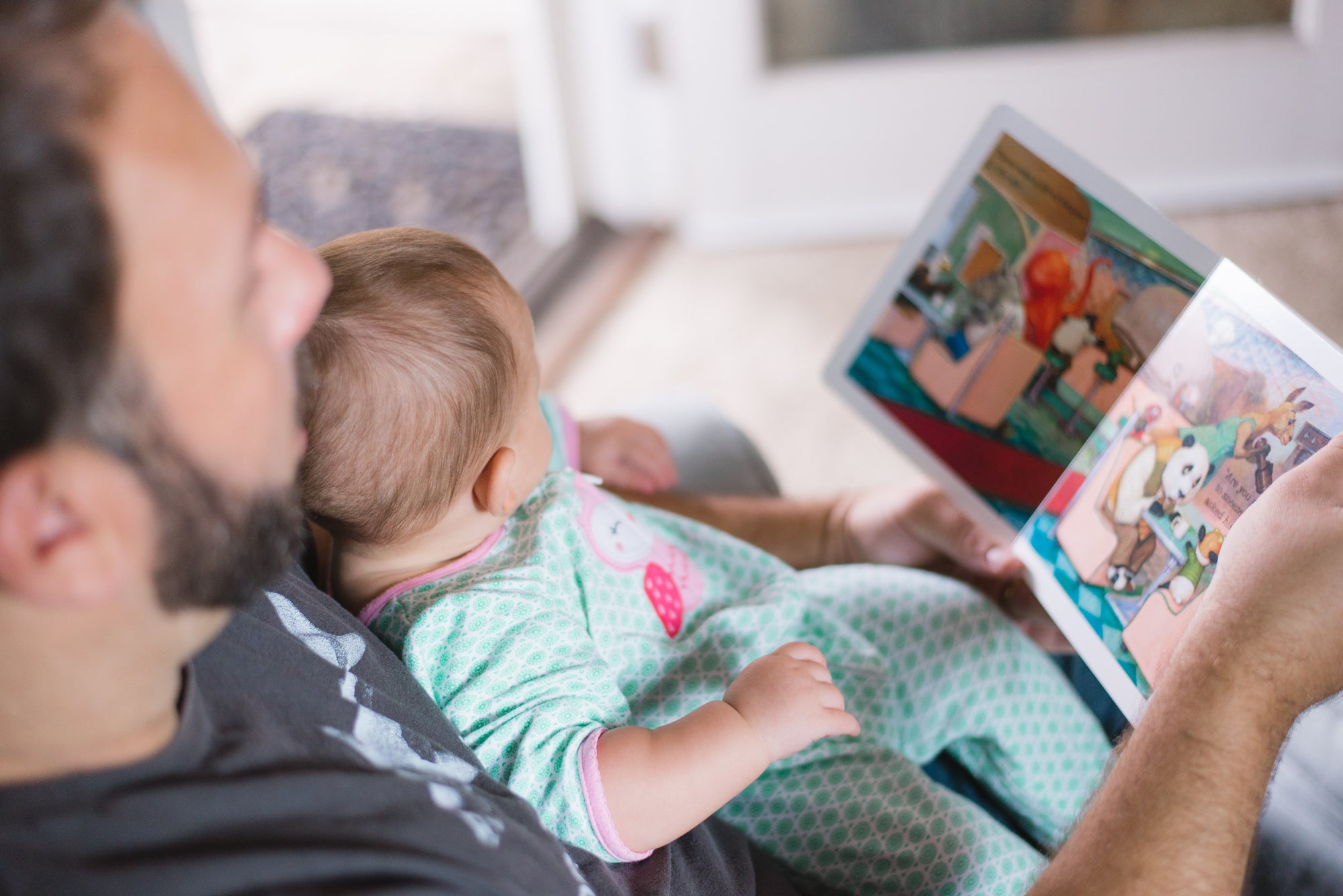 Father reading to a baby on his lap