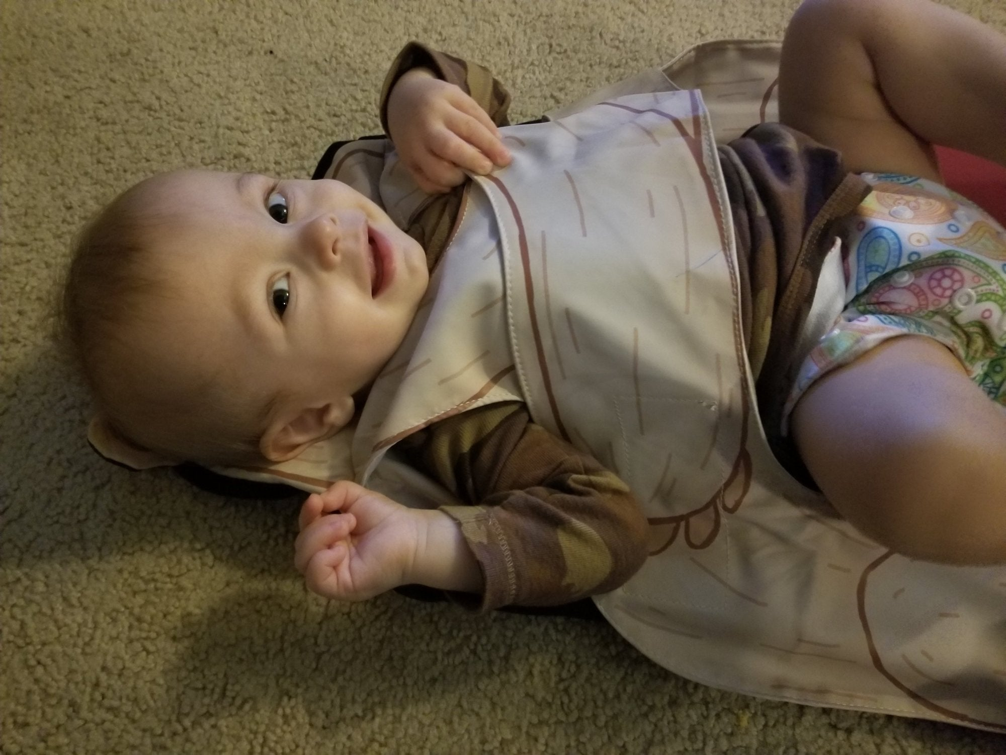 Happy toddler in The Wriggler changing pad that stops rolling over at diaper changing