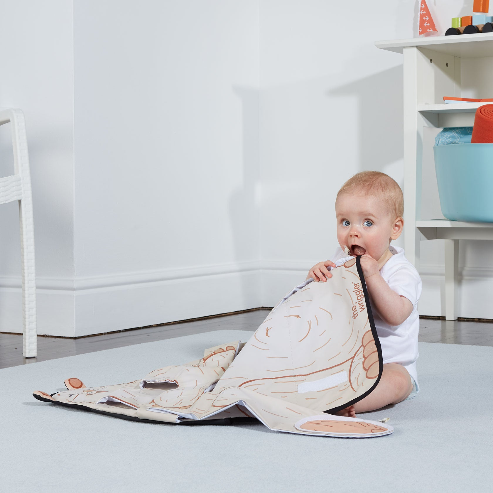 Baby placing The Wriggler changing pad in her mouth to show that the materials are BPA and phthalate free and rigorously safety tested to meet international safety standards