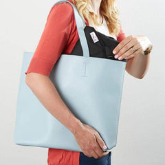 The wriggler anti roll changing mat folded and being placed in a handbag