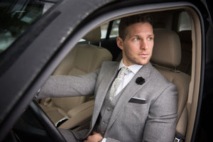 Male wearing Kings Stay Kings accessories that compliment his grey suit. The Hollywood tie is paired with a black flower lapel and batmobile pocket square. The link is to the shop all products category.