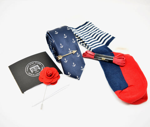 Pre-styled box with navy, red, and white colours. Kings Stay Kings boxes come with a pocket square, lapel pin, tie, tie bar, shoelaces, and socks.