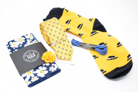 Pre-styled box with yellow and blue accents. Box comes with a pocket square, lapel pin, tie, tie bar, shoe laces, and socks.