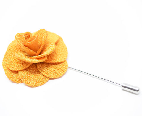 A large golden yelow flower lapel pin for a suit.