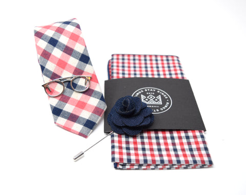 This pre-styled box comes with a navy and red checkered patterned tie and pocket square, polished silver glasses tie bar, and a navy flower lapel pin.