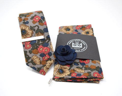 This pre-styled box has matching floral tie and pocket squares, a navy blue flower lapel pin, and a polished silver tie bar.