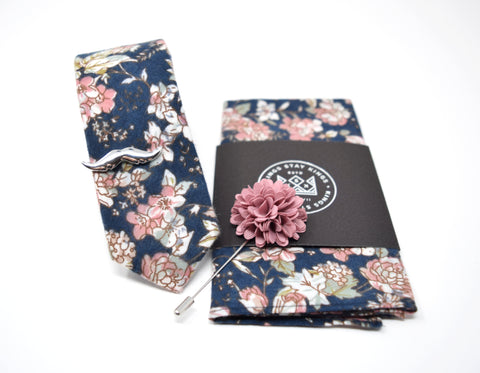 This box comes with a matching dusty rose and navy floral pattern tie and pocket square, rose lapel pin, and brushed silver moustache tie bar.