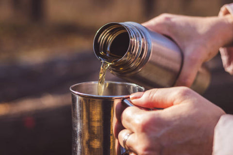 Liquid being poured into a cup from a Thermos