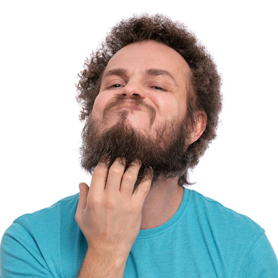 Man with curly hair scratching messy beard