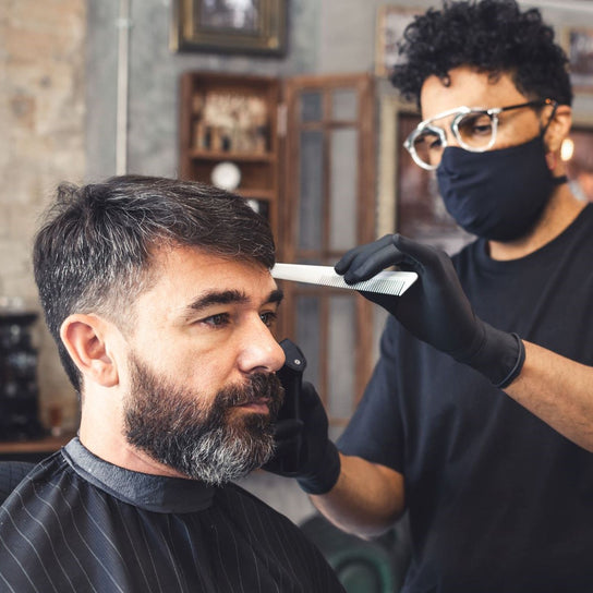 A male barber wearing a face mask cuts another man's hair holding a comb and clippers.