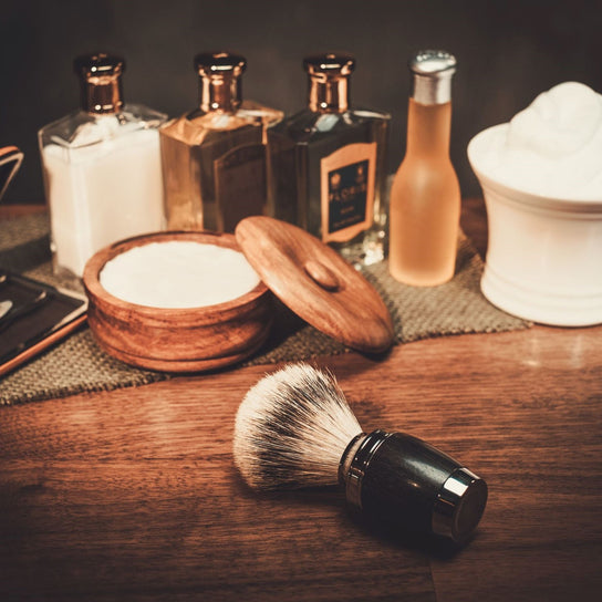 Assortment of beard maintenance items including a badger hairbrush, shaving soap, and beard oil