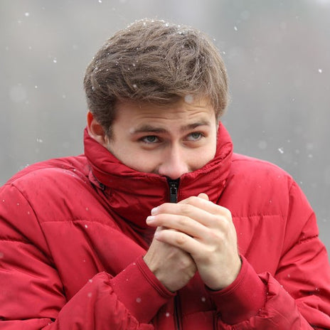 Man shivering in cold winter snowfall and rubbing hands