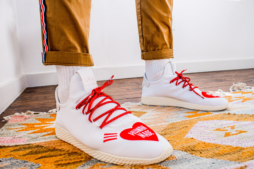 "White shoes with red laces and a red heart on the toes that says ""Human Made"""