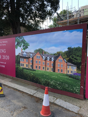Care home graphic display advertising on a hoarding around a new building