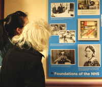 A service user enjoying reminiscence display artwork featuring a medical memory box and images relating to hospitals nurses and the NHS images