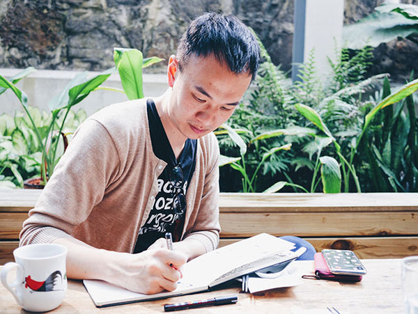 Photo of Jason Li writing in a journal on a wooden table.