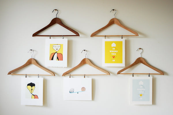 Pictures hung with coat hangers
