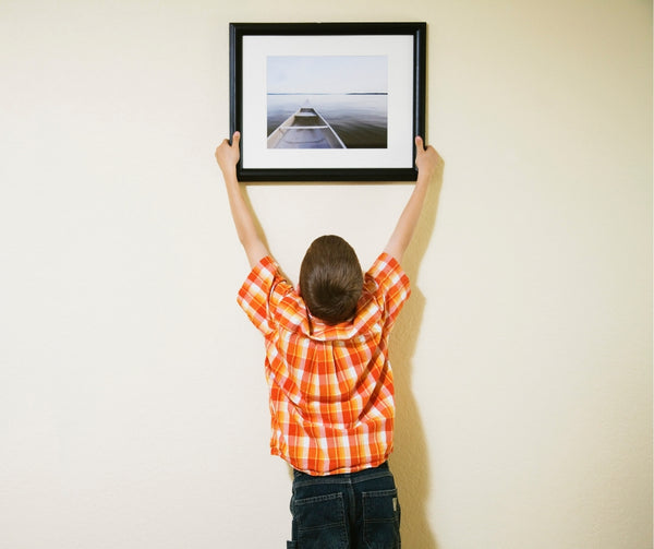 Boy hanging a picture
