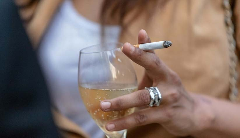 Woman holding wine glass and cigarette