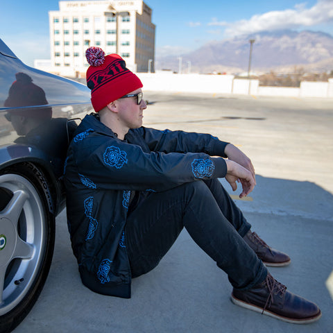 Image of vxii v12 lifestyle mens beanies maglia rossa sitting by the beamer