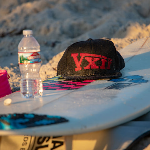 Image of vxii v12 lifestyle mens hats rosso fantastico hat on a board