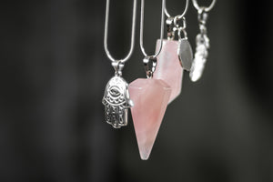 An array of of rose quartz crystals and sterling silver charms dangling in unison.