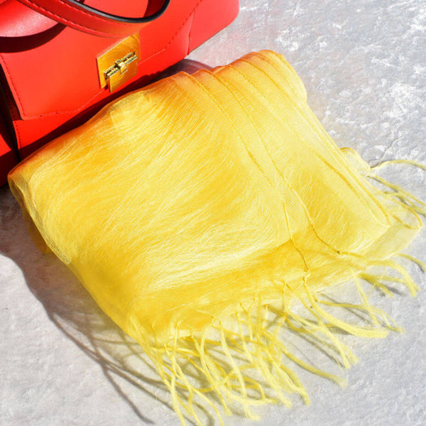 Bright Yellow Silk Scarf Folded near a Red Pocketbook