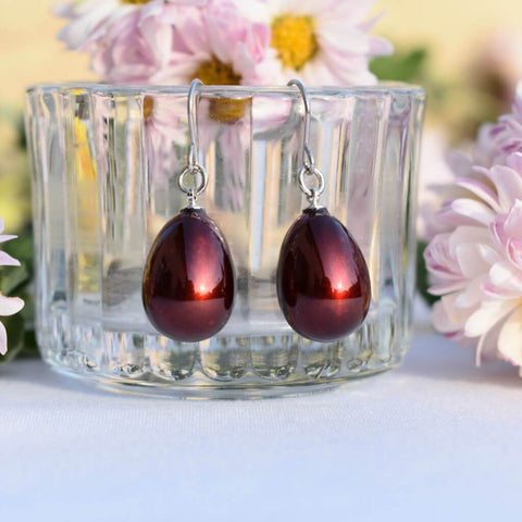 Japanese Urushi Lacquer Bordeaux-red Pierced Earrings hanging on a Glass Container Surrounded With Flowers