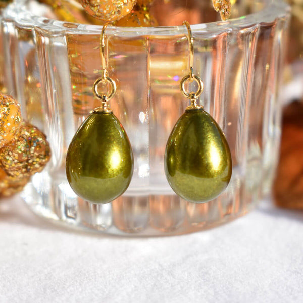 Japanese Urushi Lacquer Pistachio Green Pierced Earrings Hanging on a Clear Container with Gold Background