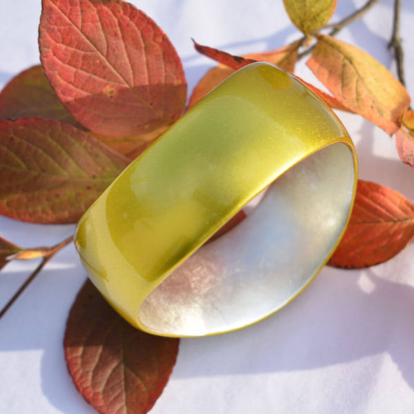 Yellow Gold Urushi Bangle Displayed on Leaves and Showing its Unique Curved Form