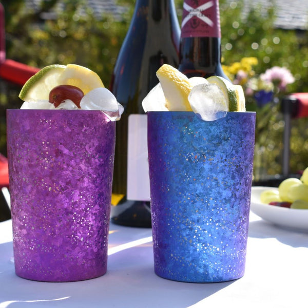 Two Sparkle Drink Tumblers, Blue and Pink, filled with Ice and Fruit on a Party Table with Craft Beer and Grapes.