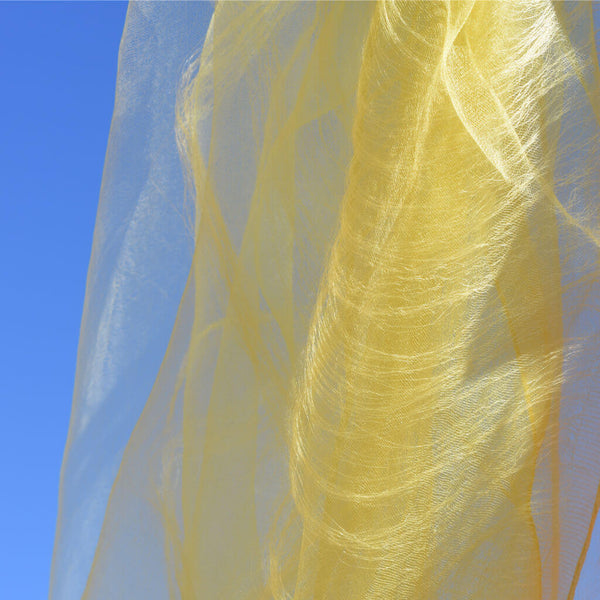 Close Up of Delicate Yellow Silk Stole against the Blue Sky