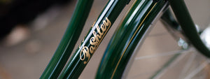 The Pashley logo in gold on the down-tube of a Pashley Princess in Regency Green.