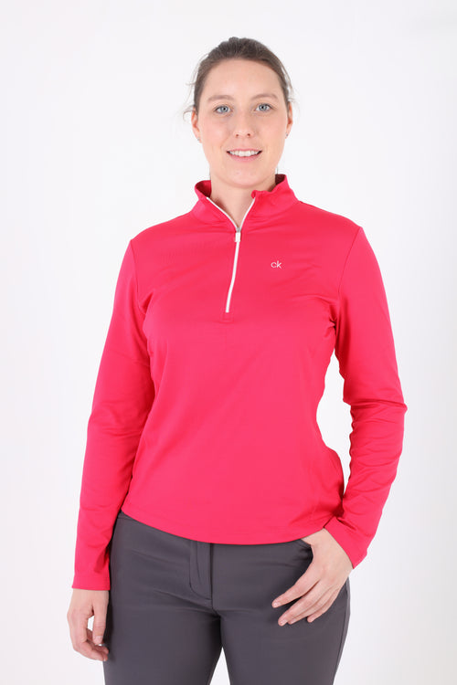 This vibrant pink ladies golf long sleeved top is a great layering piece. The stretch fabric maintains its shape wash after wash. It is stylish too and adds colour to your black winter wardrobe. Worn under a black gilet you will be as warm as toast, whilst keeping your arms free to play golf, tennis or just be active outdoors. Ladies quarter zip long sleeved top
